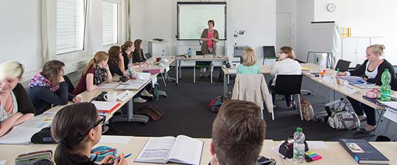 Dieses Bild zeigt ein Klassenzimmer, in dem sich Auszubildende befinden, die gerade von einer Lehrerin unterrichtet werden.