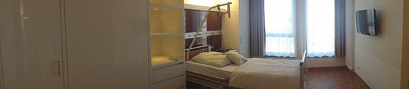 Dieses Bild zeigt das Schlafzimmer einer Familiensuite. In dem Zimmer befindet sich ein Bett und daneben ein Kleiderschrank. Der Raum hat zwei Fenster und an der Wand vor dem Bett hängt ein Fernseher.