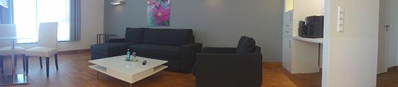 Dieses Bild zeigt das Wohnzimmer einer Familiensuite. In dem Zimmer stehen: ein Kaffeetisch mit einem Sessel und einem Sofa, ein kleiner Tisch mit zwei Stühlen und ein Regal, welches als Raumtrenner dient. Der Raum hat ein Großes Fenster.