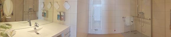 Dieses Bild zeigt das Badezimmer einer Familiensuite. Zu sehen ist eine große Dusche und ein Wachbecken, hinter dem sich eine Spiegelwand befindet. Das Zimmer ist ebenfalls mit einer Toilette ausgestattet.