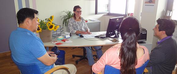 Dieses Bild zeigt eine Familie bei der Hebammensprechstunde. Die Hebamme sitzt dabei hinter ihrem Schreibtisch und berät die Familie.
