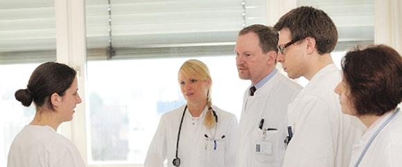 Dieses Bild zeigt Dr. Hamann und Dr. Allerlei in einer Besprechung mit drei anderen Fachkräften.