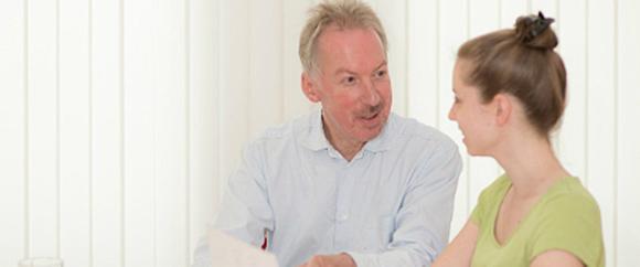 Dieses Bild zeigt Prof. Dr. Detlev Schindler während einem Gespräch mit einer Frau.