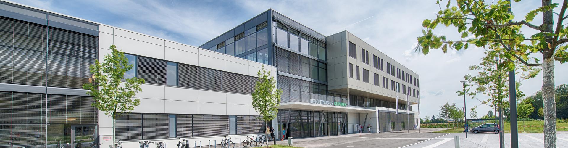 Dieses Bild zeigt den Haupteingang der Klinik am Standort Bad Homburg. Vor dem Gebäude ist eine Straße zu sehen, neben der sich Fahrradständer befinden.