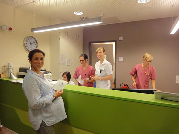 Dieses Bild zeigt den Zentralen Stützpunkt des Kreißsaals mit 4 Fachkräften hinter der Rezeption und einer schwangeren Frau an der Rezeption.