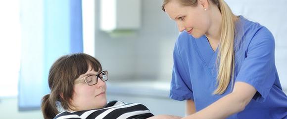 Dieses Bild zeigt eine Fachkraft der Gynäkologie und Geburtshilfe, die gerade den Bauch einer schwangeren Frau untersucht.