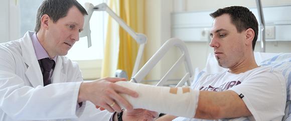 Dieses Bild zeigt Prof. Dr. med. Matthias Hansen bei der Behandlung eines Patienten der Unfallchirurgie.