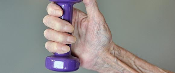 Dieses Bild zeigt eine ältere Hand. Im Griff dieser Hand befindet sich ein kleines Gewicht.