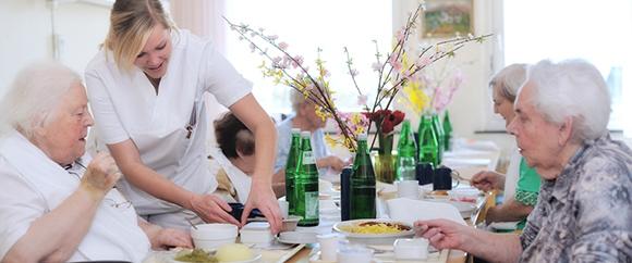 Dieses Bild zeigt eine Fachkraft der Geriatrie bei der Betreuung fünf älterer Damen während dem Essen.
