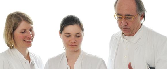 Dieses Bild zeigt Dr. med. Christoph Schäfer und zwei weitere Fachkräfte bei einer Besprechung.