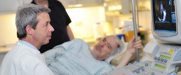 Dieses Bild zeigt Dr. Hans Hölschermann bei der kardiologischen Behandlung eines im Bett liegenden Patienten.