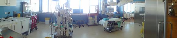 Dieses Bild zeigt einen großen Operationssaal mit einer Liege, sämtlichen Instrumenten und Tischen. Der Raum hat eine große Fensterwand.