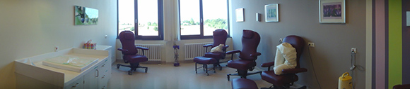 Dieses Bild zeigt ein Stillzimmer des Kreißsaals. Zu sehen ist eine Arbeitsfläche und vier bequeme Drehstühle, die für die Mütter zum stillen ihres Kindes dienen. Hinter den Stühlen befinden sich 2 Fenster