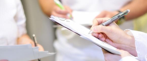 Dieses Bild zeigt drei Fachkräfte, die sich etwas auf ihren Klemmbrettern notieren.
