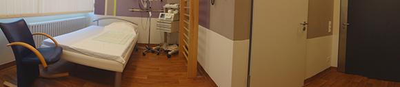Dieses Bild zeigt ein weiteres Wehenzimmer im Kreißsaal. Zu sehen ist ein großes Bett mit einem Stuhl davor und die Stationsinstrumente. Zudem hat der Raum ein Fenster.