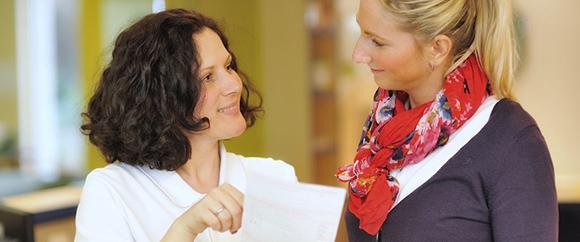 Dieses Bild zeigt eine Fachkraft, die sich gerade mit einer Frau unterhält.