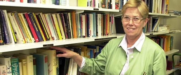 Dieses Bild zeigt ein Regal mit Büchern in der Bücherei der grünen Damen und eine Frau, die auf die Bücher hinweist.