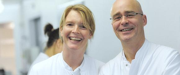 Dieses Bild zeigt zwei Mitarbeiter der Hochtaunus-Kliniken, die Sie fröhlich willkommen heißen.