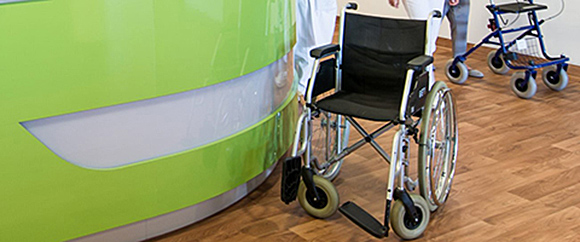 Dieses Bild zeigt einen Rollstuhl, der sich im Empfangsbereich der Klinik befindet.