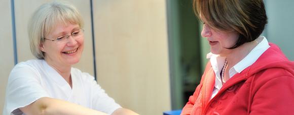 Dieses Bild zeigt eine Frau, die eine Patientin besucht.