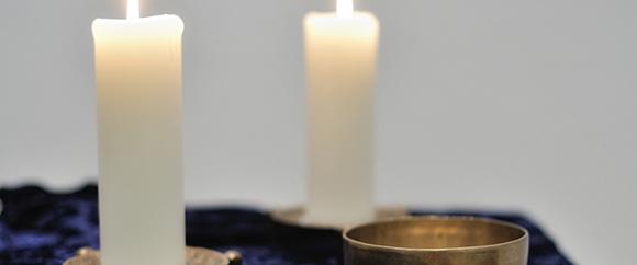 Dieses Bild zeigt zwei Kerzen und einen Behälter für Hostien auf einem Tisch.