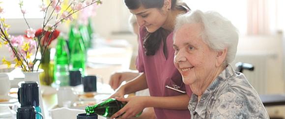 Dieses Bild zeigt eine fröhliche Patientin der Geriatrie, die von einer Mitarbeiterin der Hochtaunus-Kliniken gerade ein Glas Wasser eingeschenkt bekommt.